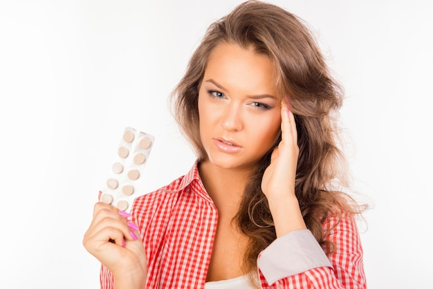 Tired woman holding tablets and suffering from strong headache