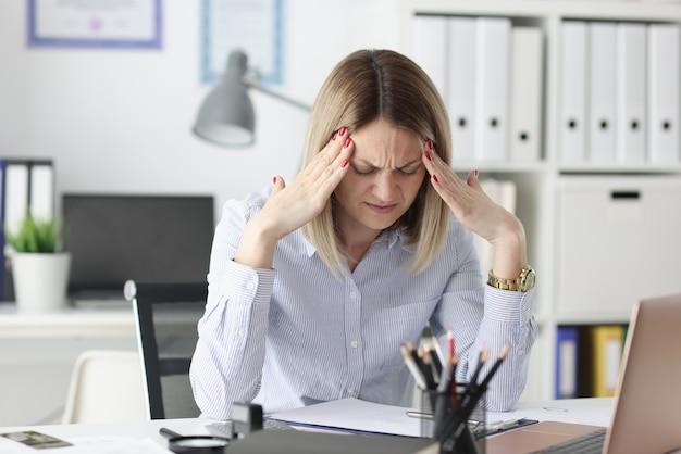 피곤한 여자는 작업 테이블에서 그녀의 사원에 그녀의 손가락을 보유하고 있습니다. 불규칙한 근무일 개념