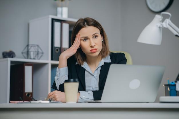 オフィスで仕事をしているときにラップトップコンピューターに座って、それからほとんど眠りについて目を覚ますメガネの疲れた女性。屋内。