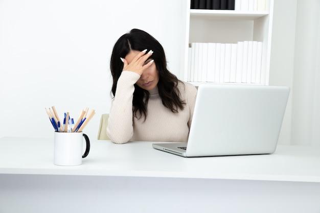 Усталая женщина в офисе сидит и работает на изолированном компьютере.