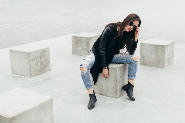 Усталая женщина в темных очках на бетонном кубе