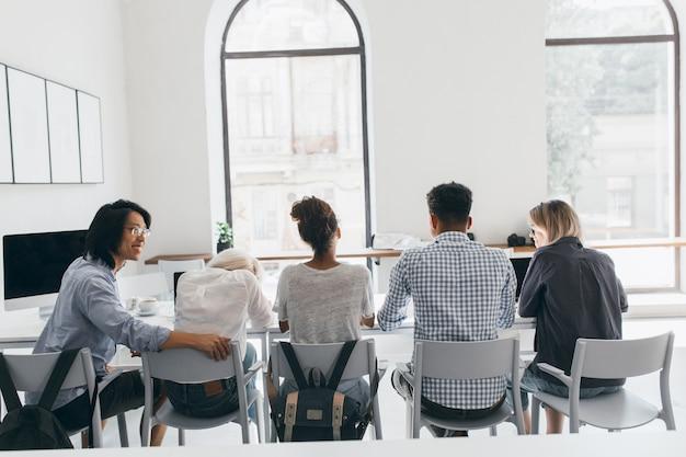 仕事の会議中にアジア人男性とアフリカ人女性の間に座っている白いシャツの疲れた女性。講義の後、大学のホールでリラックスしているアジアの学生と彼の友人の後ろからの屋内の肖像画。