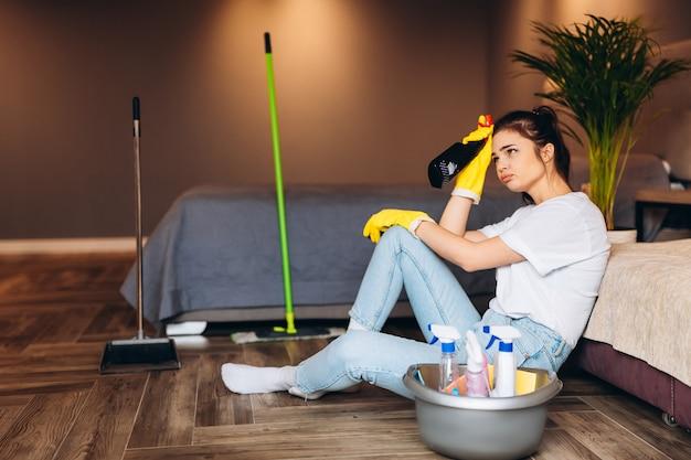手の保護と自宅でのクリーニング用品とバケツのための黄色のゴム手袋で黒髪のクリーニングと白いtシャツの疲れた女性