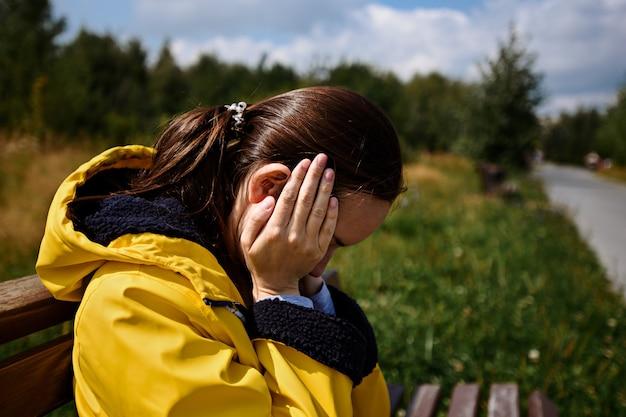 노란색 재킷에 피곤한 여자는 스트레스 상태에서 그녀의 머리에 손으로 벤치에 앉아