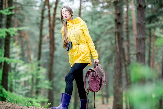 緑の森を旅しながら重いバックパックを背負って黄色のレインコートで疲れた女性