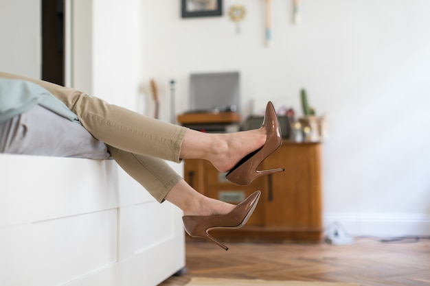 Tired woman is resting taking off her brown high-heeled shoes after work or walking, lying on the sofa. uncomfortable shoes