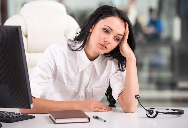 Устал женщина сидит за столом на работе в колл-центр.