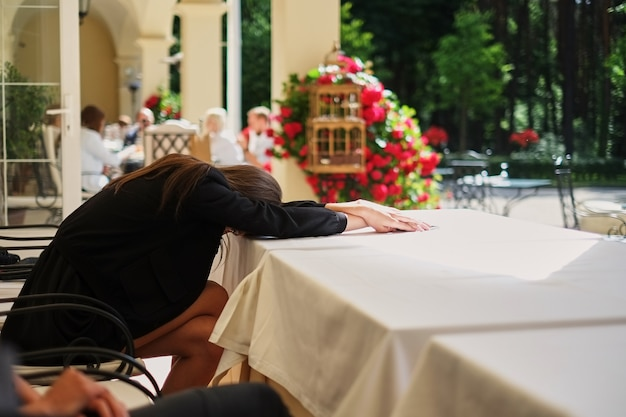 Tired woman is sitting at the table and sleeping.