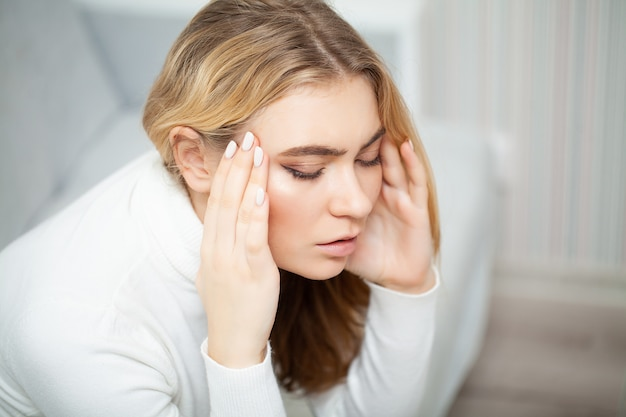 Tired woman keeping hand on her head