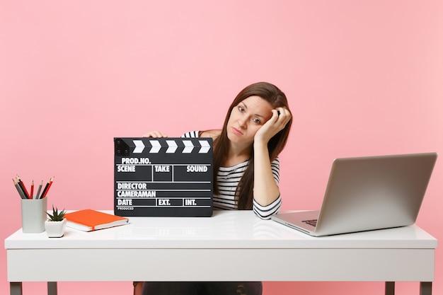피곤한 여성은 클래식 블랙 필름 제작 클래퍼보드를 들고 사무실에 앉아 노트북을 들고 프로젝트 작업을 하고 있습니다.