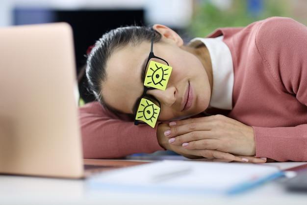 疲れた女性は彼女の目にステッカーを貼って職場に横たわっています