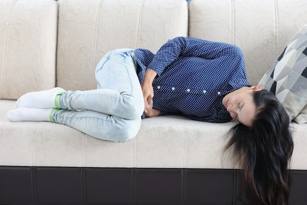 Tired woman lies on couch with abdominal pain pain in lower abdomen in women concept