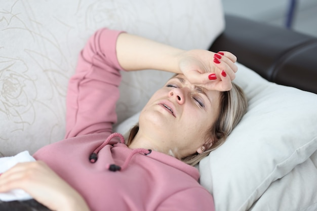 피곤한 여자는 눈을 감고 소파에 누워 이마에 손을 얹고 있다