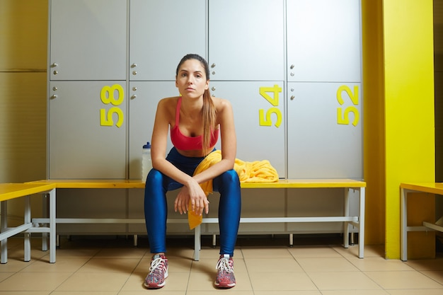 Tired woman in lockers room