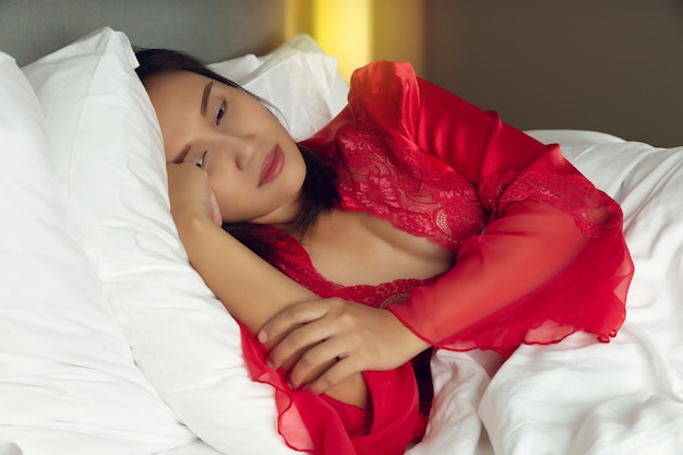 Tired woman lying in bed can't sleep late at night with insomnia. asian girl wore a satin nightgown and red robe lying on the bed awake in the bedroom