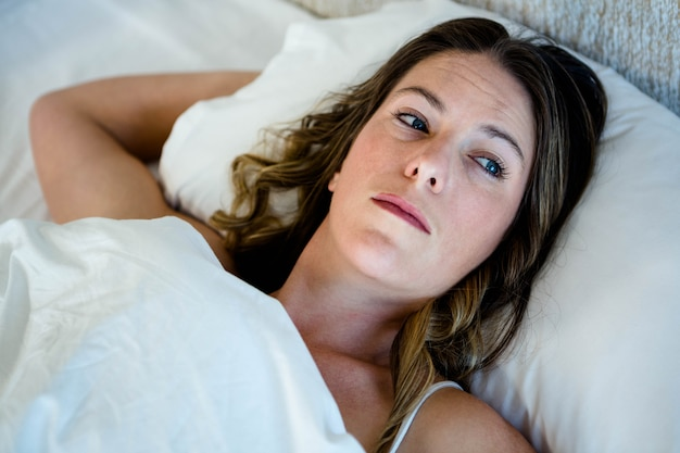Tired woman lying in her bed looking distracted