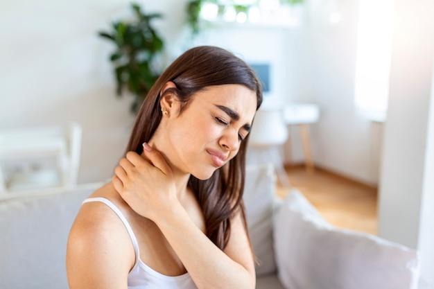 Усталая женщина массирует жесткую больную шею, напряженные мышцы, усталость от работы за компьютером в неправильной позе, чувствуя боль в суставе, плече, боли в спине. концепция фибромиалгии
