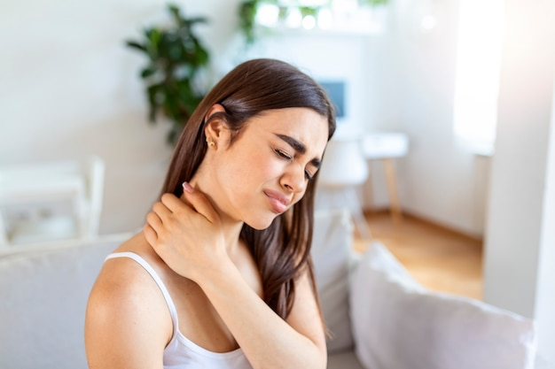 Tired woman massaging stiff sore neck, tensed muscles fatigued from computer work in incorrect posture while feeling hurt joint shoulder back pain ache. fibromyalgia concept