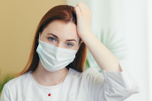 머리 뒤에 손을 잡고 얼굴에 의료 보호 마스크에 피곤된 여성 의료 종사자 의사