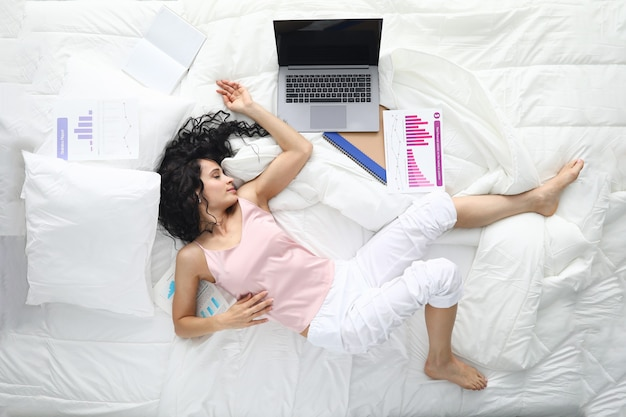 Tired woman in pajamas sleep in pose in white bed.