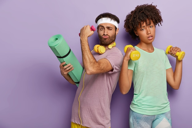 Tired woman raises two dumbbells, works on biceps and determined unshaven man carries karemat for gymnastic training