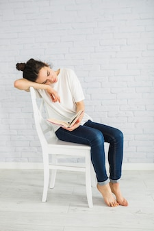 Tired woman reading book on chair