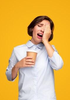 Усталая женщина протирает глаза за чашкой кофе