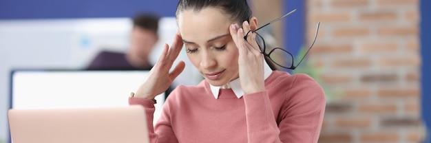 피곤 된 여자는 닫힌 된 눈으로 그녀의 책상에 앉아있다. 작업 개념에서 스트레스와 우울증