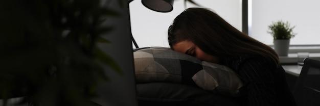 피곤한 여자는 어둠 속에서 컴퓨터 화면 앞에 앉아 있다