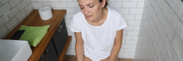 Усталая женщина сидит на унитазе и держит туалетную бумагу