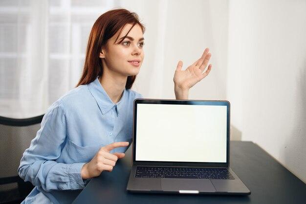 ノートパソコンの仕事の不満の前のテーブルに座っている疲れた女性