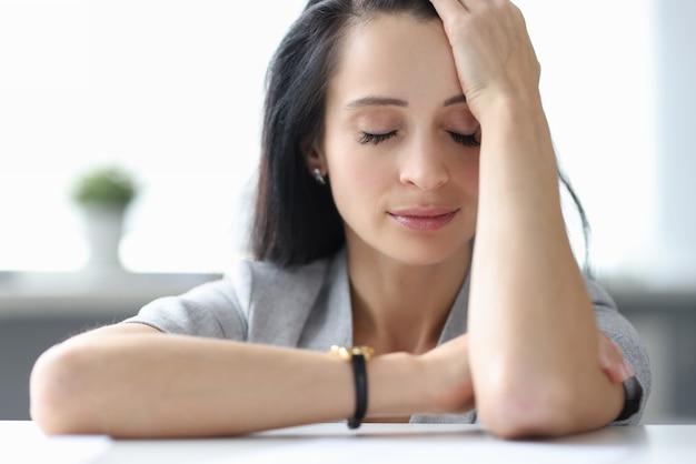 Усталая женщина, сидящая за столом с закрытыми глазами. выгорание на работе концепции