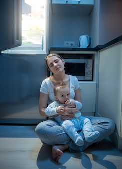 Tired woman sitting on floor at kitchen at night and feeding her baby