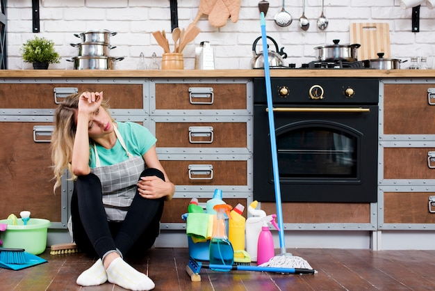 Tired woman sitting on kitchen floor with cleaning products and equipment