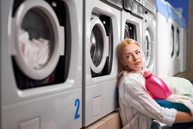 Усталая женщина сидит возле стиральных машин и грустно смотрит вверх. кавказская женщина потратила время на стирку, ожидание и скучную женщину с грязной одеждой в корзине
