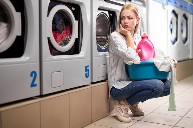 세탁기 근처에 앉아 슬프게도 찾고 피곤한 여자. 백인 여자는 바구니에 더러운 옷을 씻고, 기다리고 지루한 여성에 시간을 보냈습니다.