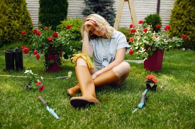 庭の芝生の上に座っている疲れた女性