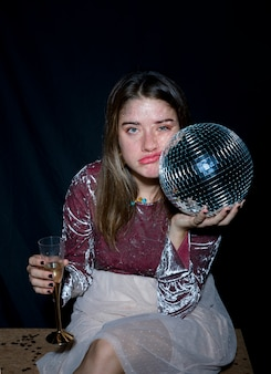 Tired woman sitting with disco ball in hand