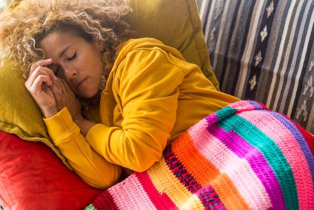 피곤한 여성은 화려한 덮개가 있는 소파에서 낮잠을 잔다 - 스트레스와 일요일 실내 생활 - 소파에서 혼자 자는 아름다운 여성