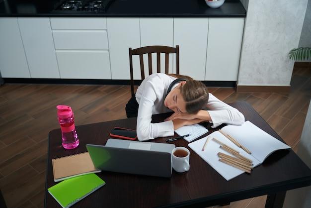 Усталая женщина спит за столом после долгого рабочего дня