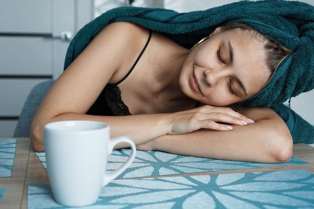 テーブルで寝ている疲れた女性。髪にタオルを着た美しい少女が一杯のコーヒーと一緒に座っています。怠惰な眠い朝