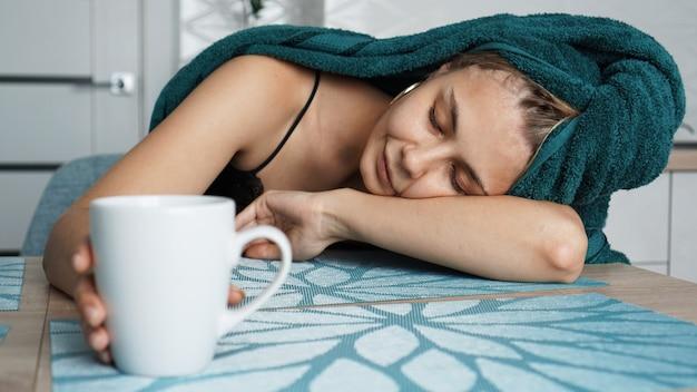 テーブルで寝ている疲れた女性。髪の上のタオルで美しい女性。マグカップに手を伸ばす