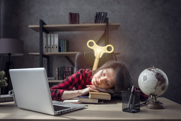 Tired woman sleeps over the books and needs a charge
