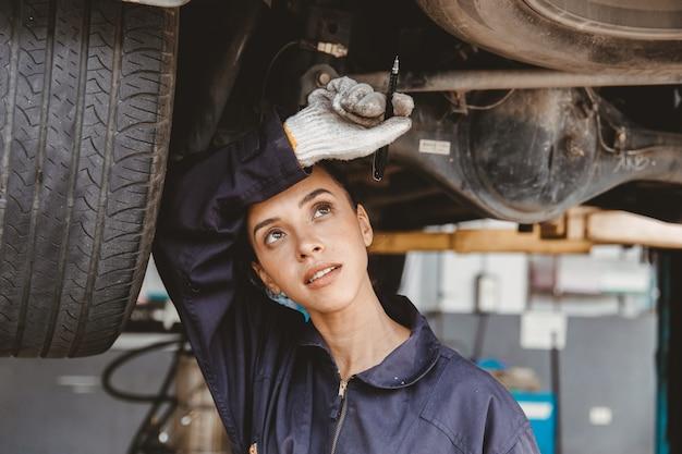 疲れた女性スタッフが自動車のガレージで汗を拭き取る危険な場所で一生懸命働いています。