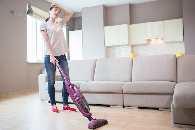 Tired woman stands and holds vacuum cleaner. it is wireless. girl holds left hand on forehead. she is cleaning the floor.