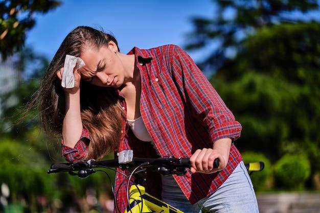 Уставшая женщина страдает от жары и жаркой погоды во время езды на велосипеде в парке летом
