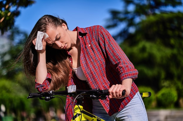 Tired woman suffers from heat and hot weather during biking in the park in summertime