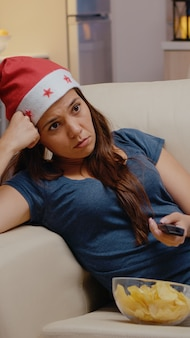 チャンネルを切り替えてテレビを見ている疲れた女性