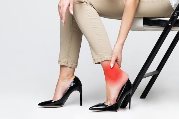 발목을 만지고 불편한 신발로 인해 다리 통증으로 고통받는 피곤한 여성