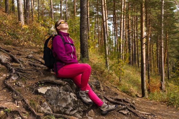 Усталая женщина-путешественница сидит отдыхая на камне на склоне горы среди осеннего леса